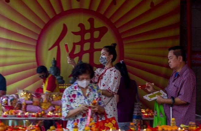 Γυναίκες στην αγορά της Κίνας φορούν μάσκες για να προστατευτούν από τον νέο κοροναϊό