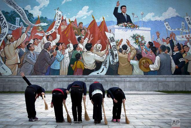 Μαθήτριες κρατώντας σκουπόξυλα, χαιρετούν το μνημείο που παρουσιάζει τον Κιμ Ιλ Σουνγκ, πριν σκουπίσουν τον χώρο γύρω του
