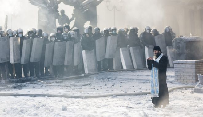 KIEV, UKRAINE - JANUARY 25: An Orthodox priest prays between police and protestors at the scene of anti-government protests near Dynamo Stadium on January 25, 2014 in Kiev, Ukraine. Violent protests in Ukraine have spread beyond the capital as President Viktor Yanukovych held crisis talks with three key opposition leaders. (Photo by Rob Stothard/Getty Images) ORG XMIT: 465073861