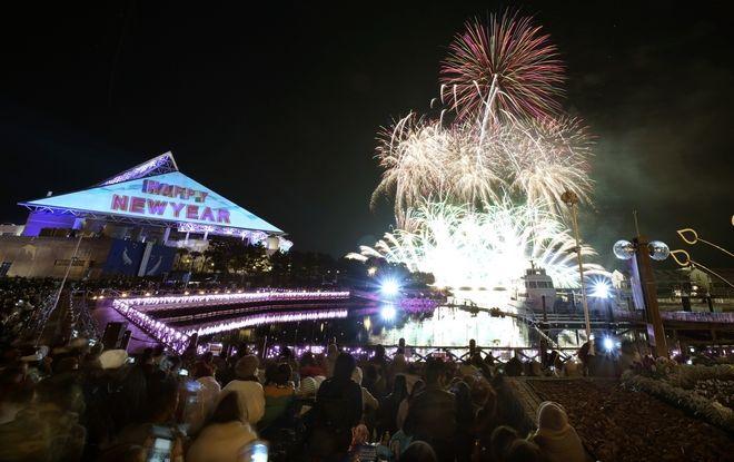 Visitors watch the fireworks display during a New Year celebration event at the Hakkeijima Sea Paradise aquarium-amusement park complex in Yokohama, southwest of Tokyo, Monday, Jan. 1, 2018. (AP Photo/Shizuo Kambayashi)