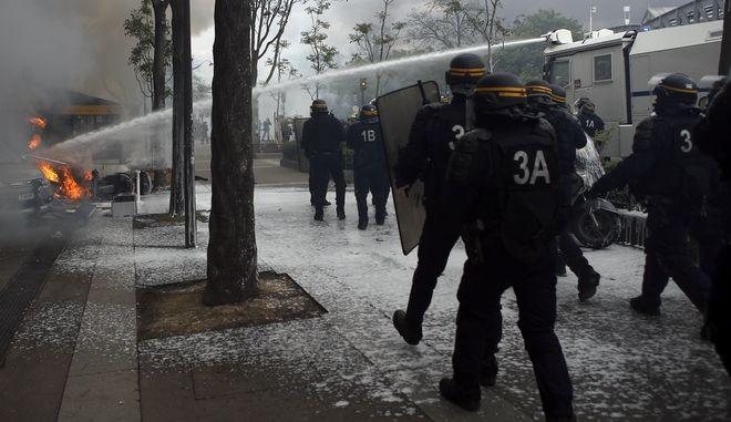 Κανόνια νερού της γαλλικής αστυνομίας προσπαθούν να σβήσουν τις φωτιές που έβαλαν κουκουλοφόροι σε οχήματα και κάδους απορριμμάτων