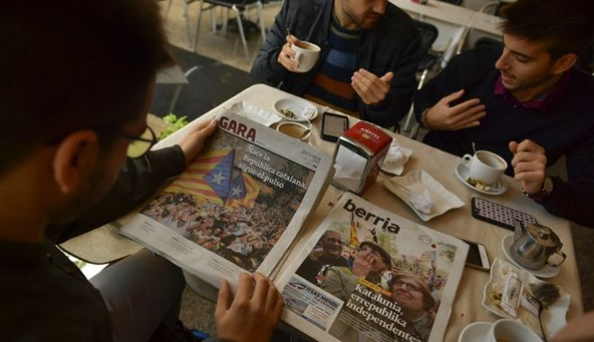 A group of catalans take a breakfast while reading some Basque nationalist newspapers which announce the independence of the Catalonia region on their front page, in Pamplona, northern Spain, Saturday, Oct. 28, 2017, a day after Catalonia's regional parliament announced the new Republic of Catalonia, and Spain's parliament moved to take direct control of the region. (AP Photo/Alvaro Barrientos)