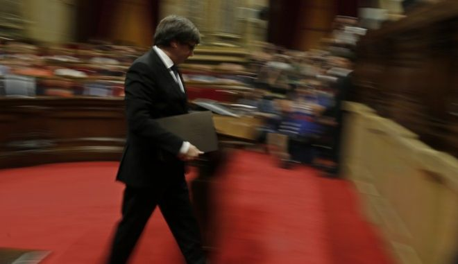 Catalan regional President Carles Puigdemont walks to the podium to make the opening speech at the parliament in Barcelona, Spain, Tuesday, Oct. 10, 2017. Puigdemont is addressing the Catalan parliament in a session that some have portrayed as the staging of an independence declaration for the northeastern region of 7.5 million, although others have said the move would only be symbolic. (AP Photo/Manu Fernandez)