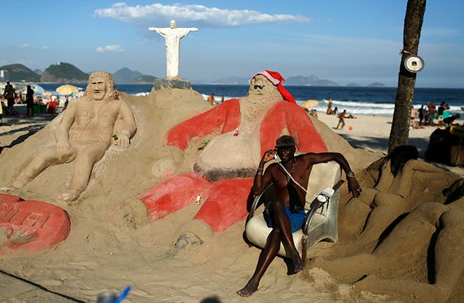 A man poses for a photo next to a Santa Claus sand sculpture on Copacabana beach in Rio de Janeiro December 3, 2014. In the Southern Hemisphere summer starts on December 1, so while countries in the north are experiencing a white Christmas with grey skies, those in the south are busy surfing and sunbathing in temperatures just shy of 100 degrees Fahrenheit (38 degrees Celsius). Picture taken December 3, 2014.  REUTERS/Pilar Olivares (BRAZIL - Tags: SOCIETY ENVIRONMENT) - RTR4IPH7