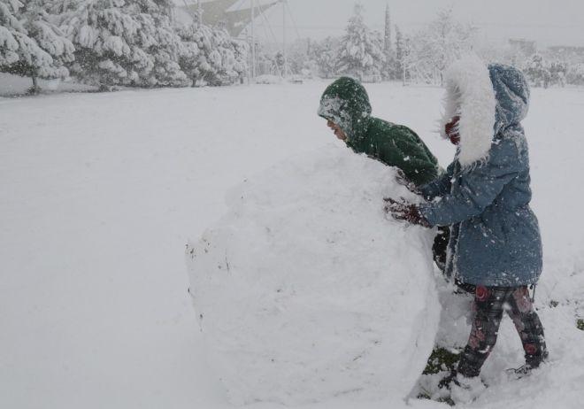 Παιδιά παίζουν με το χιόνι στο πάρκο