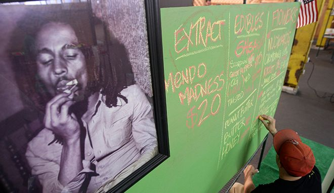 A portrait of reggae legend Bob Marley hangs next to a menu of marijuana products at the medical marijuana farmers market at the California Heritage Market in Los Angeles, California July 11, 2014. The first-ever cannabis farmers market in Los Angeles began on July 4 and opens weekly from Friday to Sunday. REUTERS/David McNew  (UNITED STATES - Tags: DRUGS SOCIETY BUSINESS) - RTR3Y8FU