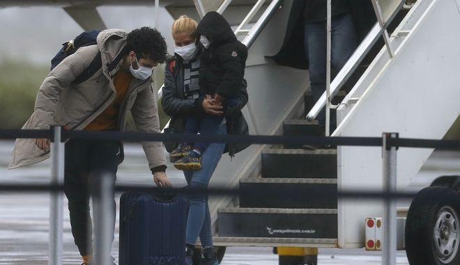 Επιβάτες φορούν μάσκες κατά την άφιξή τους από το Wuhan της Κίνας