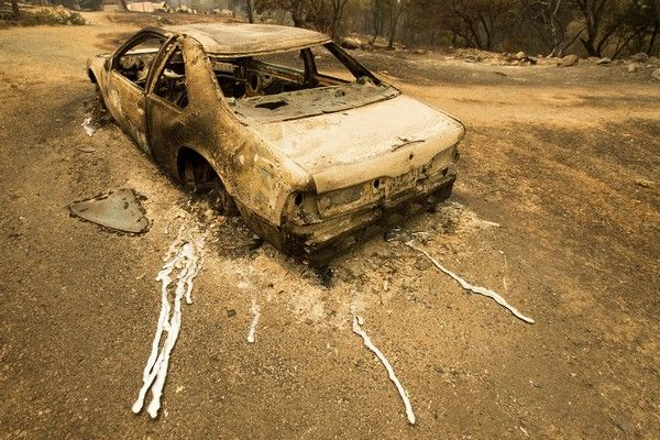 A scorched car rests next to a residence leveled by the Detwiler fire near Mariposa, Calif., on Wednesday, July 19, 2017. A surging wildfire raced through California mountains and foothills west of Yosemite National Park on Wednesday, forcing thousands to flee tiny, Gold Rush-era towns. (AP Photo/Noah Berger)