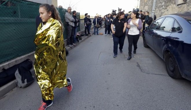 A school girl leaves her high school after an attack in a high school in Grasse, southern France, Thursday, March 16, 2017. A French high school principal and two others were shot Thursday at their school in southern France, and a 17-year-old student suspected of opening fire on them was arrested in a police raid, officials said. (AP Photo/Claude Paris)