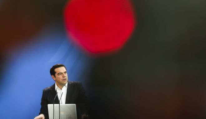 In this photo taken with a red television camera control light in the foreground, Greek Prime Minister Alexis Tsipras attends a joint statement with German Chancellor Angela Merkel prior to talks at the chancellery in Berlin, Germany, Friday, Dec. 16, 2016. (AP Photo/Markus Schreiber)