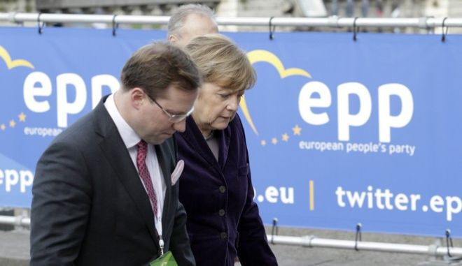 German Chancellor Angela Merkel, right, arrives with members of her delegation to a meeting of the European People's Party prior to an EU summit in Brussels on Thursday, Dec. 17, 2015. European Union heads of state meet Thursday to discuss, among other issues, the current migration crisis and terrorism. (AP Photo/Francois Walschaerts)