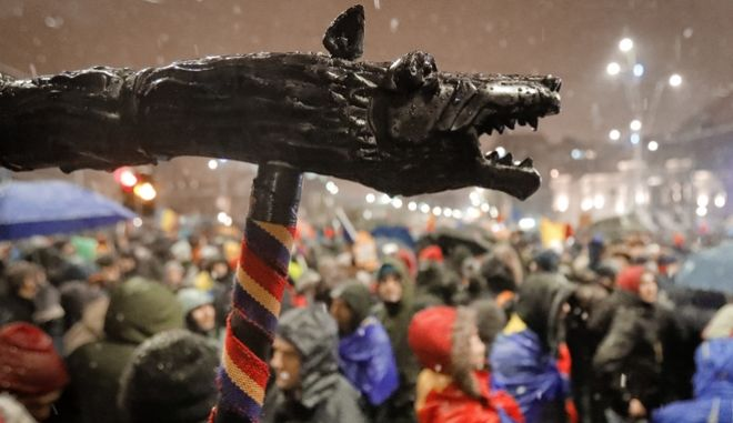 A model of a Dacian Draco, the military standard of the Dacians, an ancient population that inhabited a region of which large areas are not part of Romania, is held above the crowds during a protest in Bucharest, Romania, Saturday, Jan. 20, 2018. Tens of thousands of Romanians on Saturday protested against legislation passed by Parliament which critics say will make it harder to prosecute crime and high-level corruption, briefly scuffling with riot police as they massed in University Square.(AP Photo/Vadim Ghirda)