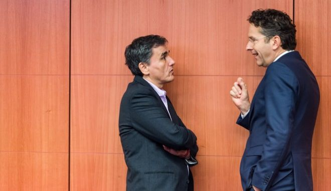 Greece's Finance Minister Euclid Tsakalotos, left, talks with Dutch Finance Minister and chair of the eurogroup of finance ministers, Jeroen Dijsselbloem, during a Eurogroup finance ministers meeting at the EU Council building in Brussels Monday, Dec. 7, 2015. (AP Photo/Geert Vanden Wijngaert)