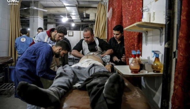 This photo released on Tuesday Feb. 20, 2018 provided by the Syrian anti-government activist group Ghouta Media Center, which has been authenticated based on its contents and other AP reporting, shows Syrian paramedics treat an injured man who was wounded by the shelling of the Syrian government forces, at a makeshift hospital, in Ghouta, suburb of Damascus, Syria. A Syrian monitoring group and paramedics say government shelling and airstrikes on rebel-held suburbs of the capital, Damascus, killed at least 98 people on Monday. (Ghouta Media Center via AP)