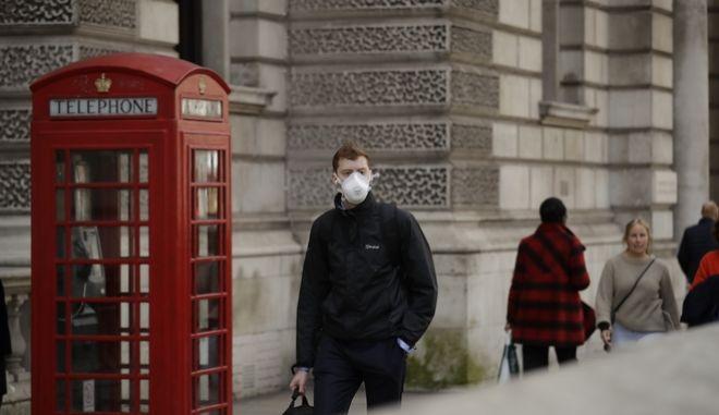 Άνδρας φορώντας μάσκα περπατάει στο Λονδίνο