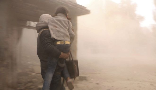 This photo released on Friday, Feb. 23, 2018 by the Syrian Civil Defense group known as the White Helmets, shows a member of the Syrian Civil Defense group carrying a girl who was wounded during airstrikes and shelling by Syrian government forces, in Ghouta, a suburb of Damascus, Syria. Syrian government warplanes supported by Russia continued their relentless bombardment of the rebel-controlled eastern suburbs of Damascus for a sixth day Friday, killing five people, opposition activists and a war monitor reported. The death toll from the past week climbed to more than 400. (Syrian Civil Defense White Helmets via AP)