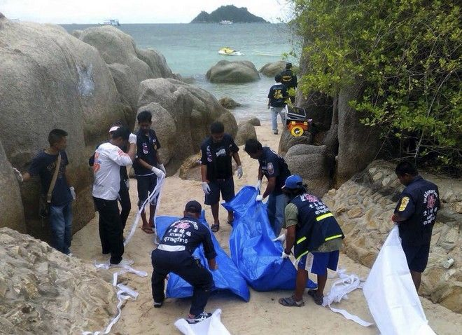 Thai officers work near the bodies of two British tourists Monday, Sept. 15, 2014 on a beach in Surat Thani  province, southern Thailand. Their bodies were discovered early Monday on a beach on Koh Tao, a small island known for its diving sites and serene beaches, police said. (AP Photo/Daily News) THAILAND OUT
