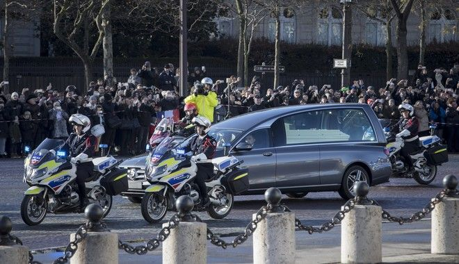 The hearse carrying the casket of French rock star Johnny Hallyday arrives at the Arc de Triomphe before rolling down the Champs Elysees avenue during a funeral procession, in Paris, France, Saturday, Dec. 9, 2017. France is bidding farewell to its biggest rock star, honoring Johnny Hallyday with an exceptional funeral procession down the Champs-Elysees, a presidential speech and a motorcycle parade  all under intense security. (AP Photo/Kamil Zihnioglu)
