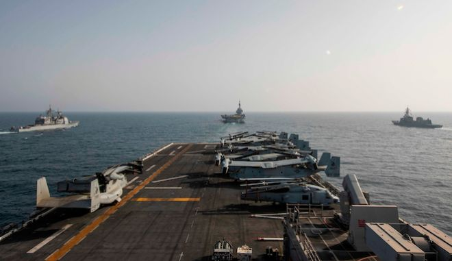 In this Friday, March 19, 2021 handout photo from the U.S. Navy, the deck of the amphibious assault ship USS Makin Island is seen in the Arabian Sea. The U.S. Navy said Sunday, March 21, 2021, that it will hold a major naval exercise alongside Belgium, France and Japan in the Mideast amid tensions over Iran's nuclear program in the region. Also seen are the U.S. Navy Ticonderoga-class cruiser USS Port Royal,  left, the French Navy aircraft carrier Charles de Gaulle, center, and the Japanese Maritime Self-Defense Force Murasame-class destroyer Ariake, right. (U.S. Navy/Mass Communication Specialist 3rd Class Ethan Jaymes Morrow, via AP)
