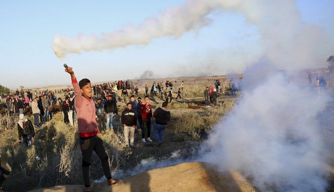 A Palestinian protester throws back a teargas canister that was fired by Israeli soldiers, during clashes on the Israeli border following a protest against U.S. President Donald Trump's decision to recognize Jerusalem as the capital of Israel, east of Gaza City, Friday, Dec. 8, 2017. (AP Photo/Adel Hana)