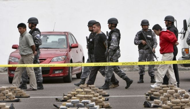 Police officers escort alleged drug dealers detained during an operation where 3.83 tons of cocaine were seized in Quito, Wednesday, Oct. 7, 2009. A laboratory, able to process up to five tons of cocaine per week, was dismantled during the operation. (AP Photo/Dolores Ochoa)