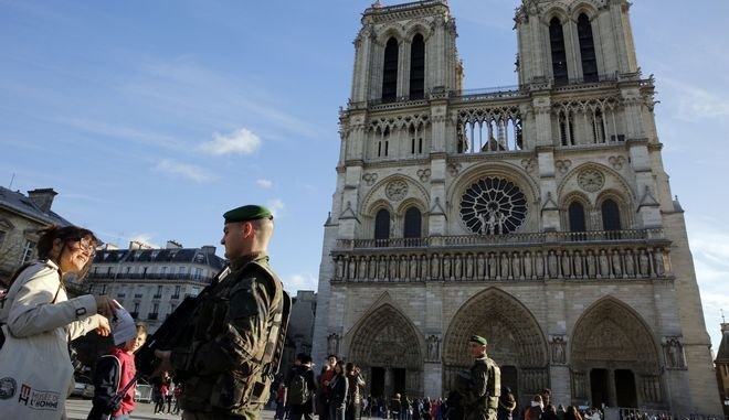 Soldiers patrol in front of Notre Dame cathedral, in Paris, Wednesday, Dec. 23, 2015. France's interior minister says the government will tighten security for churches around Christmas, amid continued concerns about potential extremist violence after deadly attacks last month. (AP Photo/Christophe Ena)