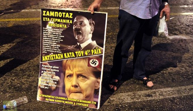 An anti-austerity protester holds a placard against the German Chancellor Angela Merkel during a demonstration in Athens on October 8, 2012. German Chancellor Angela Merkel will arrive in Greece on October 9 to lend support to its embattled government as a giant security operation goes into effect against new anti-austerity protests by unions. Thousands of police will create a safety zone for Merkel's meetings with conservative Prime Minister Antonis Samaras and President Carolos Papoulias, aiming to keep demonstrators at arm's length. AFP PHOTO/ LOUISA GOULIAMAKI