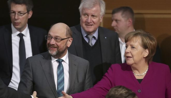 Martin Schulz, chairman of the German Social Democratic Party (SPD), front left, German Chancellor and chairwomen of the German Christian Democratic Union (CDU), Angela Merkel, front right, and Horst Seehofer, rear center, chairman of the Christian Social Union (CSU), arrive for coalition negotiations on a new German government between the Christian Unions bloc and the Social Democratic Party (SPD) in Berlin, Germany, Friday, Feb. 2, 2018. (AP Photo/Michael Sohn)