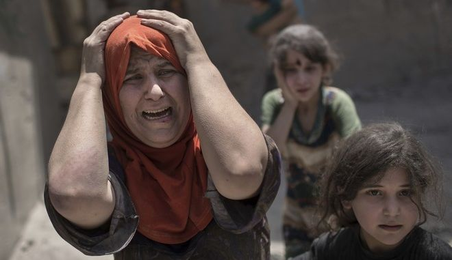 A woman screams while fleeing with her family through a destroyed alley, as Iraqi Special Forces continue their advance against Islamic State militants, in the Old City of Mosul, Iraq, Sunday, July 2, 2017. (AP Photo/Felipe Dana)