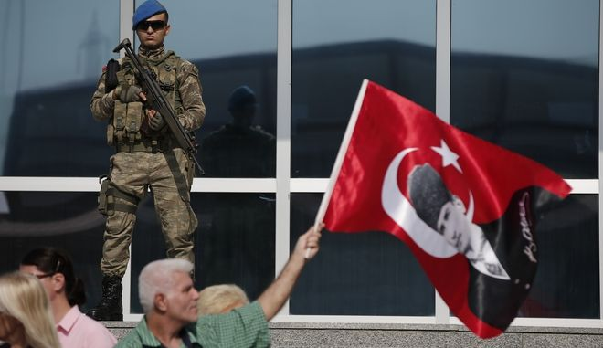 Under the watchful eye of a Turkish army soldier standing guard outside a court, protesters, one holding a Turkish flag with an image of Mustafa Kemal Ataturk, the founder of Modern Turkey, demonstrate against a trial of journalists and staff from the Cumhuriyet newspaper, accused of aiding terror organizations, in Silivri, Turkey, Monday, Sept. 11, 2017. The trial against journalists and staff from Cumhuriyet newspaper staunchly opposed to President Recep Tayyip Erdogan continues in Istanbul, a case that has added to concerns over rights and freedoms in Turkey. (AP Photo/Emrah Gurel)