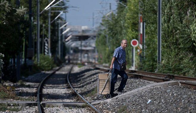 Ένας άνδρας διασχίζει τις ράγες καθώς τα τρένα θα παραμείνουν ακίνητα στους σταθμούς λόγω της 24ωρης πανελλαδικής απεργίας στις 30 Μαϊου.