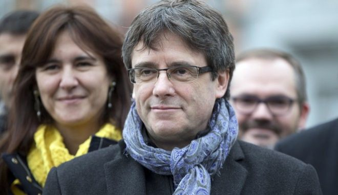 Ousted Catalan leader Carles Puigdemont, center, stands with elected Catalan lawmakers of his Together for Catalonia party at a park in Brussels on Friday, Jan. 12, 2018. (AP Photo/Virginia Mayo)