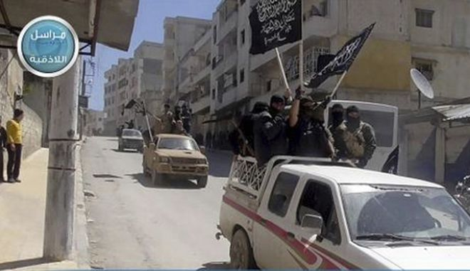 FILE - In this file photo posted on the Twitter page of Syria's al-Qaida-linked Nusra Front on April 25, 2015, which is consistent with AP reporting, Nusra Front fighters stand on their vehicles and wave their group's flags as they tour the streets of Jisr al-Shughour, Idlib province, Syria. The Syrian government has forced thousands of insurgents and their families to relocate to the northern Idlib province as part of truce deals, a move that rebels suspect is aimed at gathering them far from the capital where they can later be eliminated. The al-Qaida stronghold is now home to several insurgent groups, some with radical ideologies, and has been compared to Kandahar, the Talibans onetime seat of power in Afghanistan. (Al-Nusra Front Twitter page via AP, File)