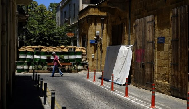 A woman walks by a wall with barrels and sand bags that block a road to the Turkish Cypriots breakaway north part between the U.N buffer zone that divided the Greek and Turkish Cypriots controlled areas in central divided capital Nicosia, Cyprus, Friday, June 30, 2017. U.N. Secretary-General Antonio Guterres has joined high-level talks aimed at reunifying ethnically divided Cyprus amid hopes he can help nudge rival sides toward a breakthrough. Two days of talks at the Swiss resort of Crans-Montana have made no real progress on the core issue of the island's future security that could unlock an overall peace accord. (AP Photo/Petros Karadjias)