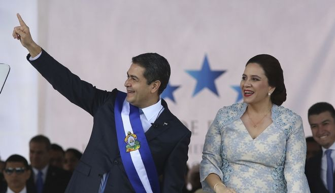 Honduran President Juan Orlando Hernandez acknowledges supporters accompanied by his wife Ana Garcia, during the presidential inaugural ceremony at the National Stadium in Tegucigalpa, Honduras, Saturday, Jan. 27, 2018. Hernandez has been sworn in for a second term amid protests against the November election that was marred by irregularities and allegations of fraud. (AP Photo/Fernando Antonio)
