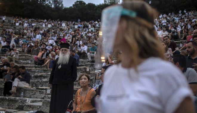 Ιερέας, τουρίστες και εργαζόμενη με μάσκα στην Επίδαυρο