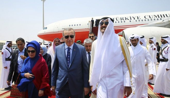 Turkey's President Recep Tayyip Erdogan, centre, accompanied by his wife Emine, left, is greeted by Emir of Qatar Sheikh Tamim bin Hamad Al Thani, right, upon his arrival, in Doha, Qatar, Monday, July 24, 2017. Erdogan has arrived in Qatar on the final leg of a Gulf tour aimed at forging a resolution to the diplomatic standoff gripping the Gulf nation and four fellow Arab countries. (Presidency Press Service via AP, Pool)