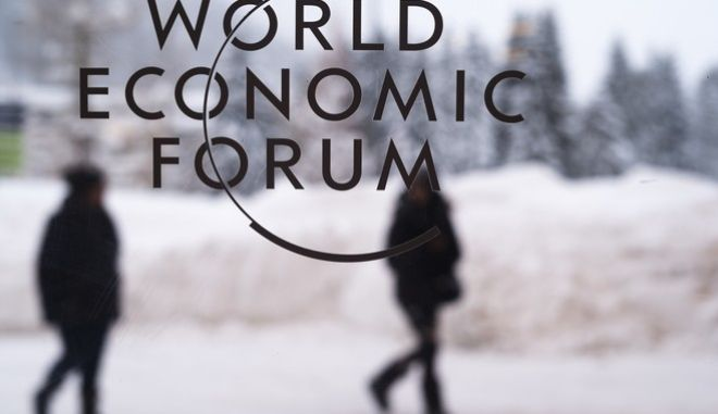 Two persons walk behind the logo of the World Economic Forum at the meeting's conference center in Davos, Switzerland, Sunday, Jan. 21, 2018. The meeting brings together entrepreneurs, scientists, chief executives and political leaders from Jan. 23 to 26. (AP Photo/Markus Schreiber)