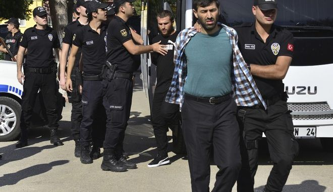 Turkish police officers escort men, suspected of being Islamic State group members,  at a court in Adana, southern Turkey, Thursday, Nov. 2, 2017. Security officials say police have detained 283 suspected Islamic State group militants in Turkey in the past 11 days. A security directorate statement released on Thursday also said police seized 66 improvised explosive devices during the anti-IS operations conducted in 25 provinces across Turkey. (Caglar Ozturk/DHA-Depo Photos via AP)