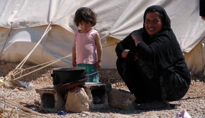 """Γυναίκα πρόσφυγας φτιάχνει φαγητό στον καταυλισμό που έχει στηθεί στο στρατόπεδο """"Ευθυμιόπουλου"""" στο Κουτσοχερο Λάρισας την Πέμπτη 31 Μαρτίου 2016. Στον καταυλισμό φιλοξενούνται περισσότεροι από 1500 πρόσφυγες οι περισσότεροι οικογένειες με μικρά παιδιά. Όλοι ζητούν τους επισκεφθεί κάποια κυβερνητική ή κοινωνική οργάνωση που θα μπορεί να τους δώσει απαντήσεις για το θέμα της επανένωσής τους με συγγενείς τους στη Βόρεια και Δυτική Ευρώπη. (EUROKINISSI/ΘΑΝΑΣΗΣ ΚΑΛΛΙΑΡΑΣ)"""