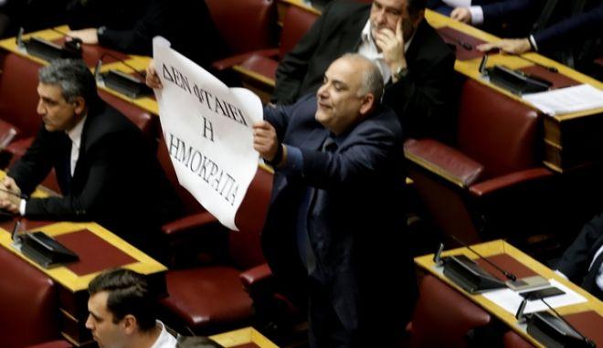Ο Γιώργος Σαρίδης με το πανό στη Βουλή
