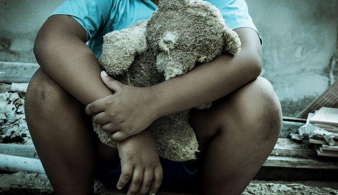 Vintage tone,Sad boy sitting alone with old teddy bear