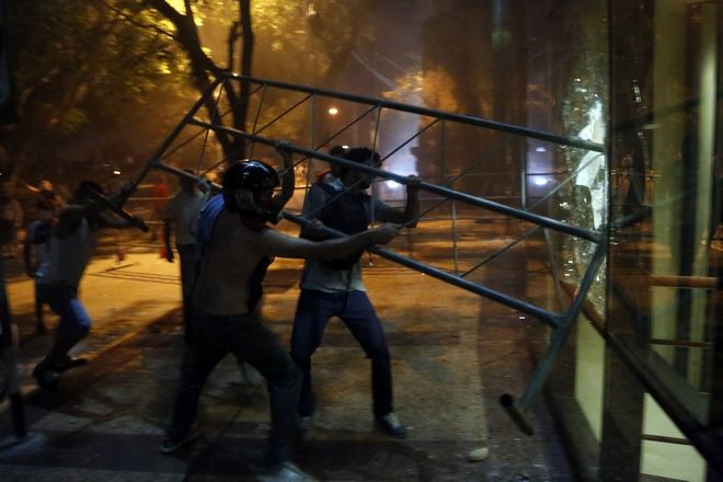 People ram a barrier into the Congress building during clashes between police and protesters opposing an approved proposed constitutional amendment that would allow the election of a president to a second term,  in Asuncion, Paraguay, Friday, March 31, 2017. Some protesters broke through police lines and entered the first floor, where they set fire to papers and furniture. Police used water cannon and fired rubber bullets to drive demonstrators away from the building while firefighters extinguished blazes inside. (AP Photo/Jorge Saenz)