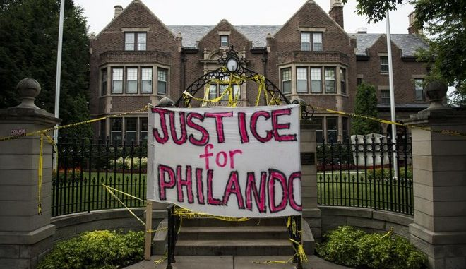 """ST. PAUL, MN - JULY 07: A sign reading, """"Justice for Philando,"""" and police tape are draped over the entrance of the Governor's Mansion following the police shooting death of a black man on July 7, 2016 in St. Paul, Minnesota. Philando Castile was shot and killed last night, July 6, 2016, by a police officer in Falcon Heights, MN. (Photo by Stephen Maturen/Getty Images)"""