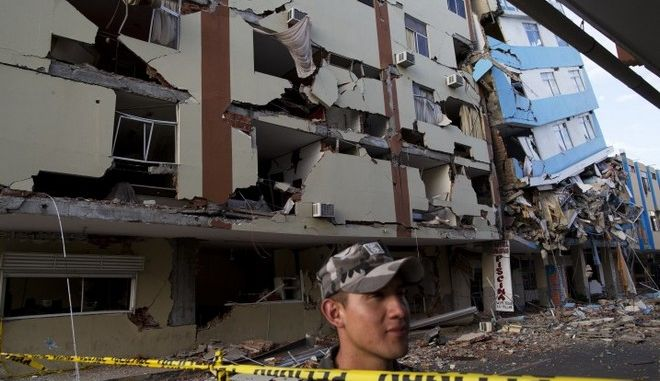 An air force soldier stands guard trying to prevent looting in the earthquake ravaged business district of Manta, Ecuador, Monday, April 18, 2016. A Saturday night quake left a trail of ruin along Ecuadors Pacific Ocean coast. Hundreds died and thousands are homeless. (AP Photo/Rodrigo Abd) (AP Photo/Rodrigo Abd)