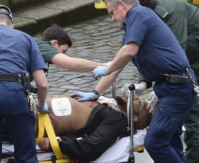 A man is treated by emergency services outside the Houses of Parliament London, Wednesday, March 22, 2017.  London police say they are treating a gun and knife incident at Britain's Parliament