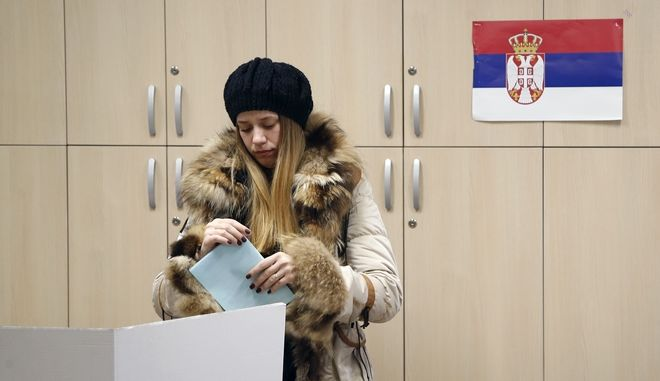 A woman prepares her ballot for the local elections at a polling station in Belgrade, Serbia, Sunday, March 4, 2018. Serbia's liberal opposition sees Sunday's municipal assembly election as a chance to weaken Serbia's President and Progressive Party leader Aleksandar Vucic. (AP Photo/Darko Vojinovic)