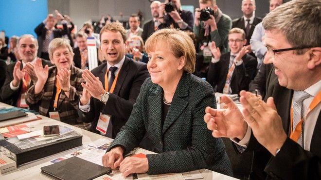 dpatopbilder Die CDU-Vorsitzende Angela Merkel sitzt am 09.12.2014 in Köln (Nordrhein-Westfalen) beim Bundesparteitag der CDU bei der Bekanntgabe des Wahlergebnisses zwischen dem CDU-Landesvorsitzenden in Mecklenburg-Vorpommern, Lorenz Caffier (r), sowie dessen Generalsekretär Vincent Kokert. Foto: Michael Kappeler/dpa