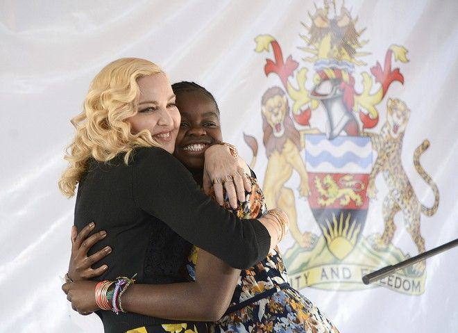 US singer Madonna, hugs her adopted girl, Mercy, at the opening of The Mercy James Institute for Pediatric Surgery and Intensive Care, located at the Queen Elizabeth Central Hospital in the city of Blantyre, Malawi, Tuesday, July 11, 2017. Madonna was in Malawi on Tuesday for the official opening of a hospital children's wing funded by her charity and named after one of the four children the pop star has adopted from the impoverished southern African nation. (AP Photo Thoko Chikondi)