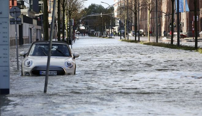 A car stands in a flooded street near the harbor in Hamburg, northern Germany, Sunday, Oct. 29, 2017.  High winds struck the country causing flooding and damage in northern and eastern Germany. (Bodo Marks/dpa via AP)